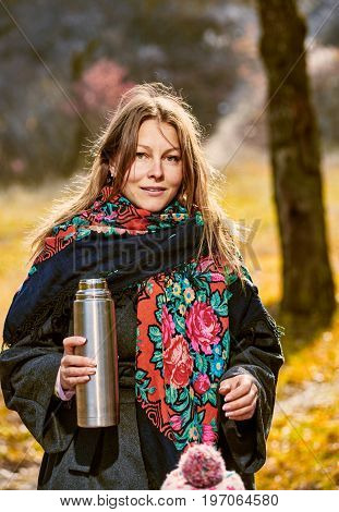 Pretty woman having walk in autumn forest and holding thermos with tea