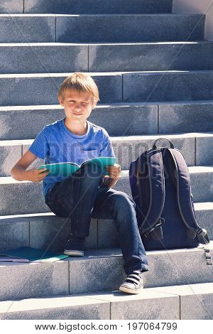 Schoolboy reading books. Smiling kid doing homework outdoors. Back to school concept.