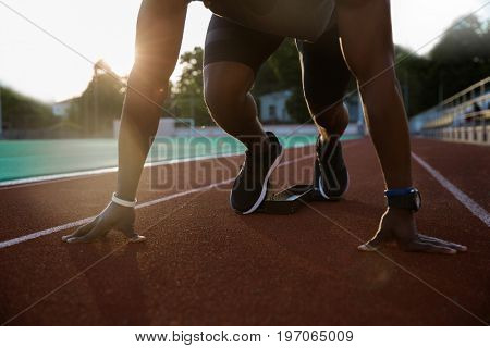 Cropped image of a young african male sprinter getting ready to start the race