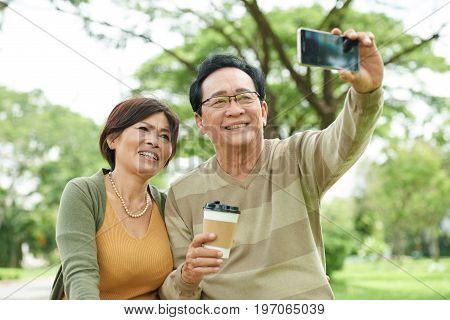 Joyful Vietnamese senior couple taking selfie in park
