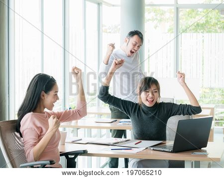 Cheering happy business people , Happy business team with arm raised sitting at desk in office during an office monthly meeting success, business concept background , Activity moving blurred concept