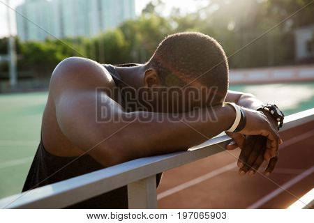 Close up of a tired african sportsman leaning on the railing and resting after workout at the stadium