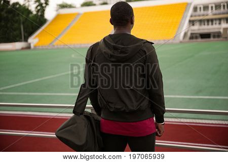 Back view of a young sportsman with bag standing at the stadium