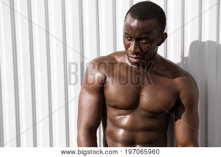 Close up of a young tired african sportsman resting against white wall