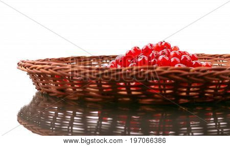 Healthful red currant in a brown basket isolated over the white background.  Juicy seasonal berries. Delicious red currant for a breakfast. Rustic berries for vegetarian snacks.