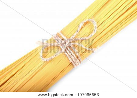 A top view on long pasta noodles tighten with a little rope with a bowtie. Nutritious noodles isolated on a white background. Delicious flour pasta. Traditional italian cuisine.