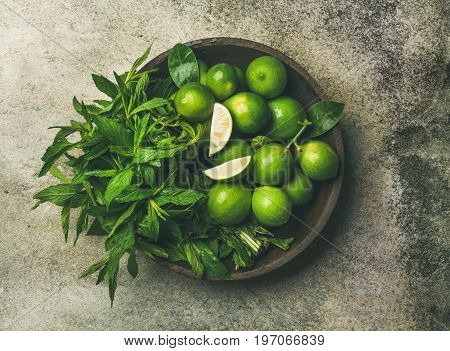 Flatlay of freshly picked organic limes and mint leaves for making cocktail or lemonade in wooden plate over grey concrete stone background, top view