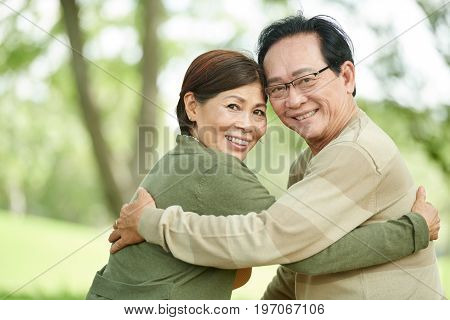 Smiling senior Asian couple hugging and turning back to look at the camera