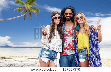 summer holidays, travel and people concept - smiling young hippie friends in sunglasses showing peace hand sign over tropical beach background