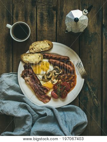 Flat-lay of traditional English breakfast with fried eggs, sausages, mushrooms, sauted tomatoes, bacon, beans, butter toasts and coffee on rustic wooden background, top view