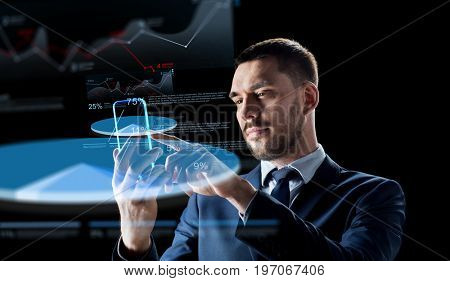 business, augmented reality and modern technology concept - businessman working with transparent smartphone and virtual charts projections over black background