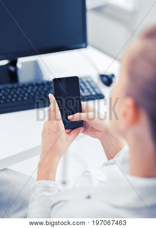 business, office, school and education concept - businesswoman with smartphone in office