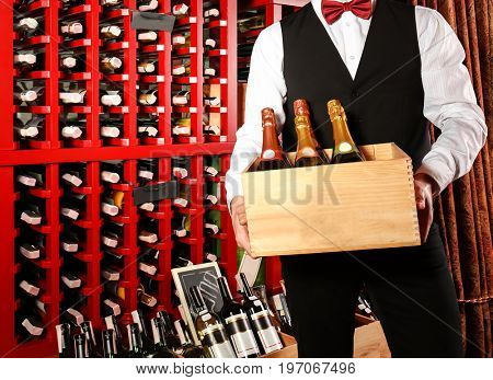 Sommelier with wine bottles in wooden crate at store