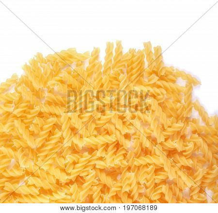 Close-up of the heap of uncooked fusilli noodles isolated on a white background. Traditional Italian fusilly pasta full of nutrients. Tasty and organic carbohydrate ingredients.
