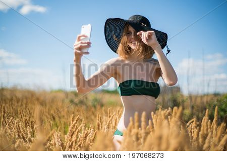Young beautiful woman in hat doing selfie on mobile phone in sunny day on field