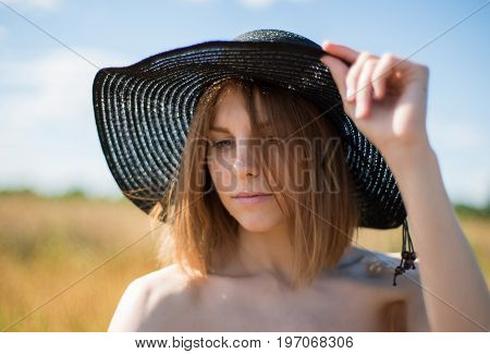 Portrait of a young beautiful woman in a hat on the field
