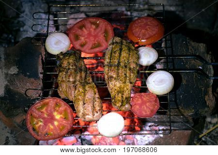 Cooking meat with vegetables in the grill