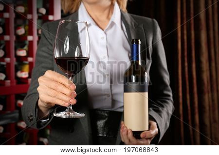 Sommelier with glass of wine and bottle at store