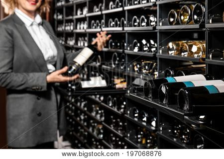 Rack with wine bottles and woman on background
