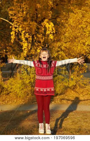 very happy little girl in the park in autumn with yellow leaves. adolescent with arms outstretched outdoor