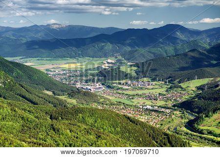 City Ruzomberok from hill Hrdos (Ostre) in Mala Fatra national park in Slovakia. Low Tatras mountains at backround