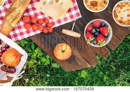 Overhead photo of picnic with apples, fresh fruit in plastic container, piece of Dutch cheese, quiches, baguette, and a corkscrew, on a rustic wooden board on top of green grass, with place for text