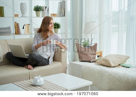 Woman having cup of coffee and looking through the window