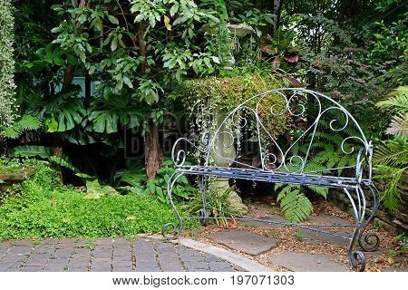 White colored wrought iron bench in the garden with tropical plants
