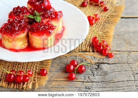 Sweet pancakes with berries jam. Bright pancakes with red currant jam and a mint leaf on a white plate and an old wooden table. Beautiful summer breakfast. Rustic style
