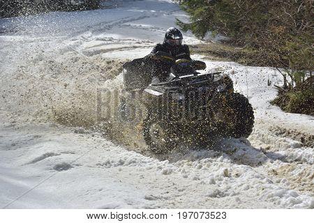 man driving a quad bike in the winter field