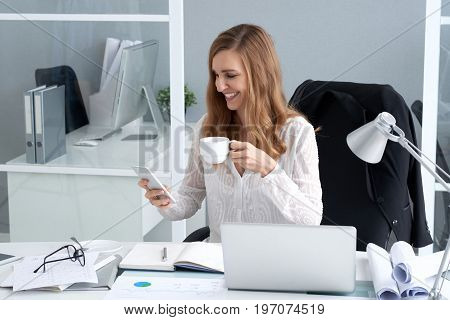 Happy business lady drinking coffee and reading text message