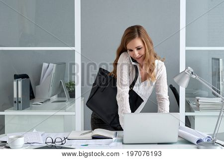 Smiling female entrepreneur talking on the phone and checking e-mail on laptop