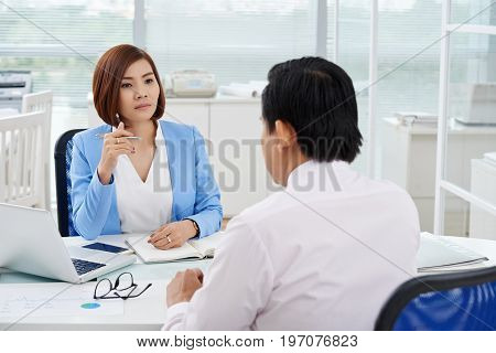 Beautiful Vietnamese business lady listening to ideas of her coworker at meeting