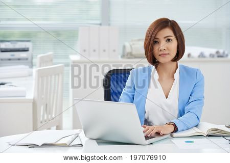 Portrait of pretty Vietnamese business lady working on laptop at her workplace