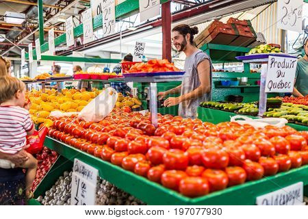 Montreal, Canada - May 28, 2017: Happy Smiling Man Selling Produce By Tomato Stand With Sample Slice