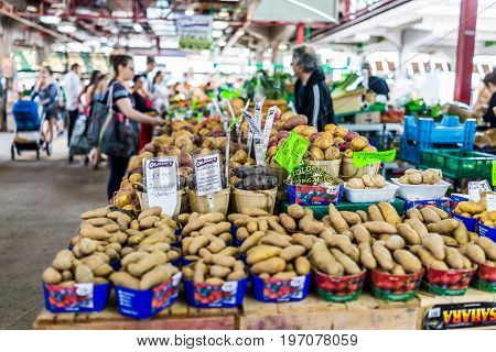 Montreal, Canada - May 28, 2017: Man Selling Produce By Stands At Jean-talon Farmers Market With Dis