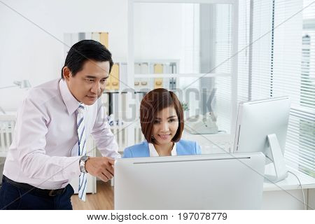 Vietnamese coworkers analyzing information on computer screen