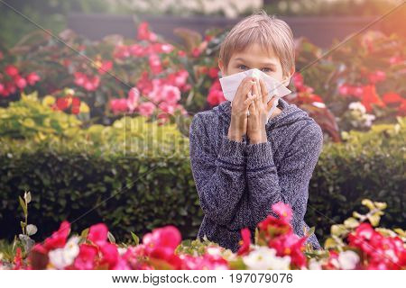 Child having allergy. Boy sitting outdoor with tissue in city park