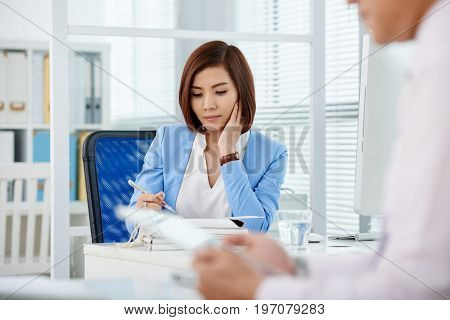 Portrait of pretty young business lady working with document on her table