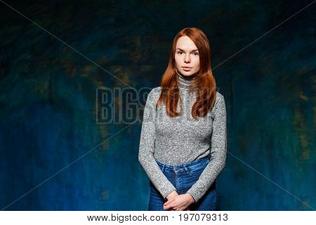 portrait of fashion woman in blue jeans and gray pullover. beauty model girl with luxurious red hair. hairstyle. holiday makeup.