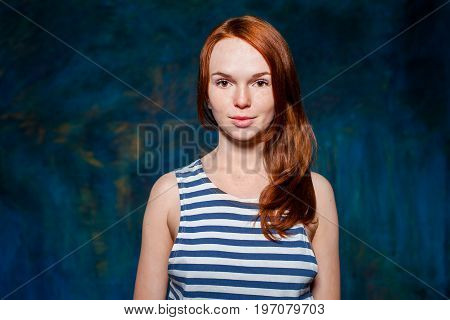smiling redhead girl in vest with white and blue stripes over dark blue background. beauty model woman with luxurious red hair. hairstyle. holiday makeup