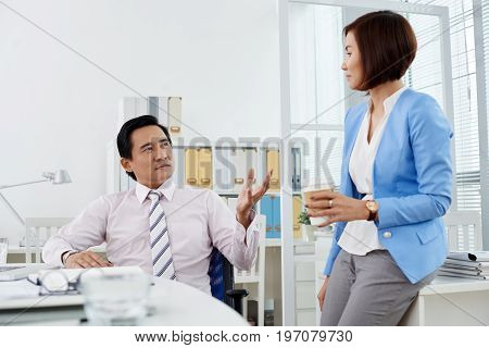 Two colleagues having conversation during coffee break