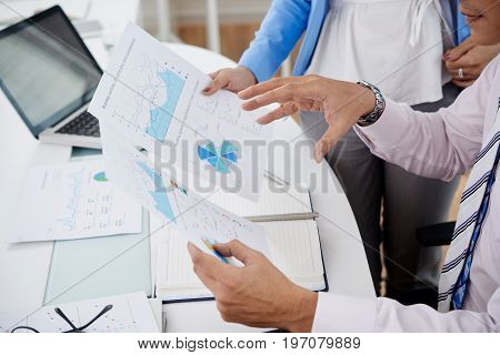 Close-up image of coworkers discussing business charts and graphs at the meeting