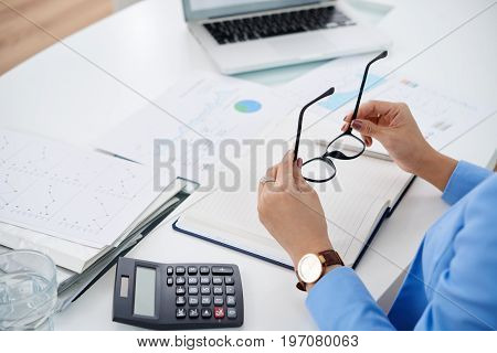 Hands of business woman putting on her glasses before working with documents