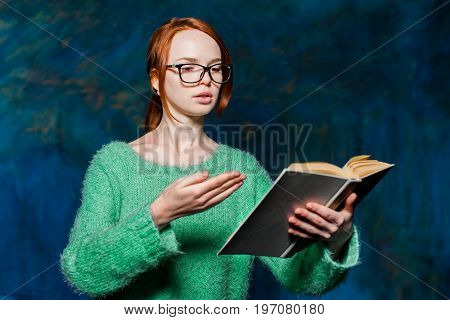 young beautiful redhead girl in green sweater and glasses over magic dark blue background