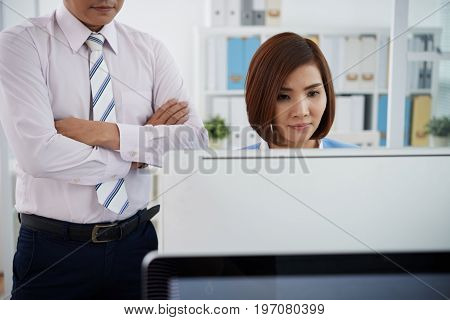 Businessman standing behind the back of new employee and controlling her work