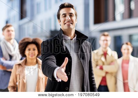 business, education, gesture and corporate concept - group of happy people and man giving hand for handshake on city street