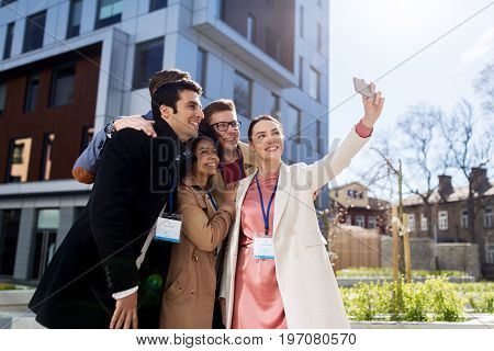business, education and corporate concept - international group of people with conference badges taking selfie by smartphone on city street