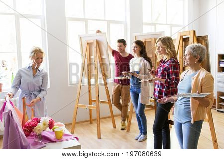 painting, education and people concept - group of artists or students and teacher with still life and easels at art school studio