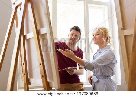 creativity, education and people concept - man artist or student with palette and teacher painting on easel at art school studio